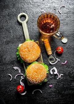 Hamburgery z plastrami piwa i cebuli. na czarnym tle rustykalnym