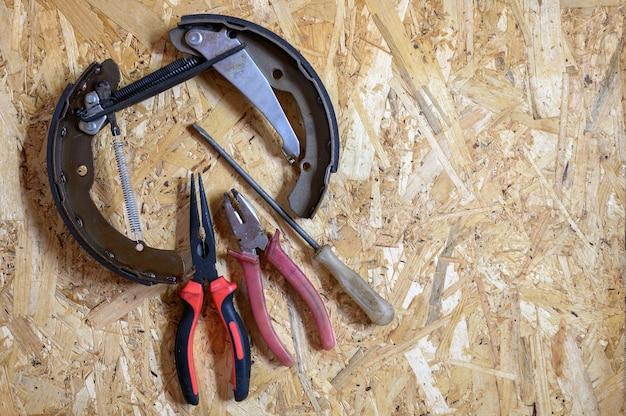 Hamulec bębnowy samochodu zdemontowany i zestaw różnych narzędzi ręcznych do naprawy lub zestaw narzędzi mechanika samochodowego na arkuszu sklejki osb w tle. leżał płasko, widok z góry
