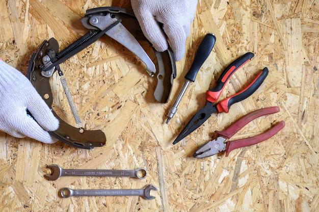 Hamulec bębnowy samochodu zdemontowany w męskich rękawiczkach i zestaw różnych narzędzi ręcznych do naprawy lub zestaw narzędzi mechanika samochodowego na arkuszu sklejki osb w tle. leżał płasko, widok z góry