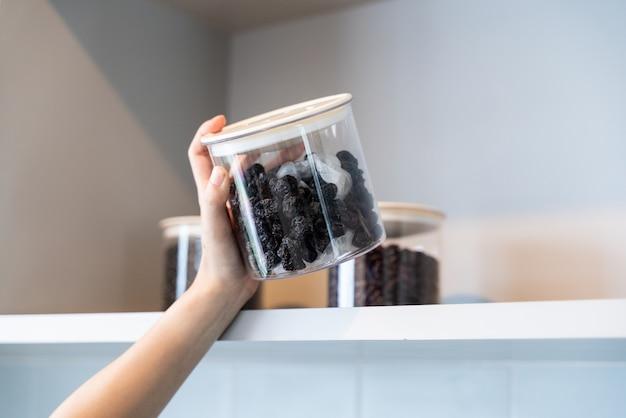 Hand hold bottle z suchej śliwki w kuchni