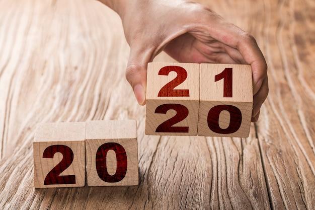 Hand przerzuca blok zmieniający się z 2020 na 2021