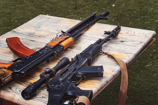 Handel bronią. różne karabiny na ladzie w sklepie z bronią. potajemna sprzedaż broni. nielegalny zakup broni. broń palna na stole. nielegalna transakcja sprzedaży broni. karabin maszynowy,