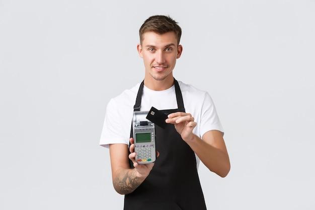 Handel detaliczny, kawiarnia i restauracja, koncepcja pracowników. przyjazny i uprzejmy przystojny kelner dający terminal pos, klient płacący za kawę kartą kredytową, uśmiechnięty radośnie, białe tło