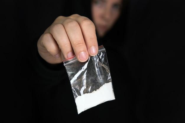 Handlarz narkotyków podający narkotyki w plastikowej torbie, kokainę, heroinę, speed lub inne narkotyki na ciemną czerń