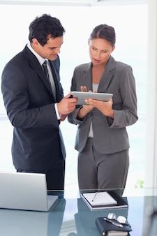 Handlowiec wyjaśniający funkcjonalność tabletu swojemu koledze