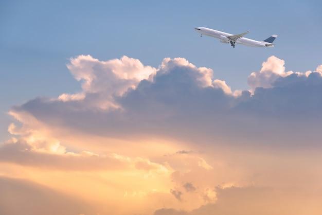 Handlowy samolot lata nad wschodu słońca niebem i chmurnieje tło