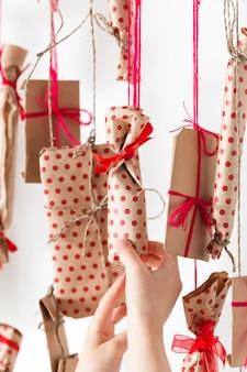 Handmade kalendarz adwentowy wisi na białej ścianie. prezenty zapakowane w papier rzemieślniczy i związane czerwonymi nitkami i wstążkami. drewniany kij i wiele prezentów