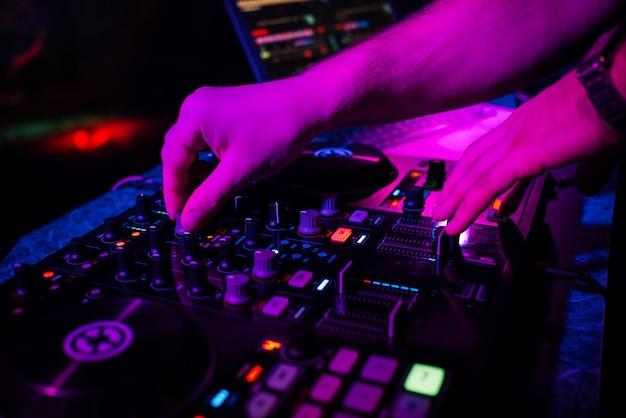 Hands dj gra i miksuje muzykę na kontrolerze muzycznym na imprezie