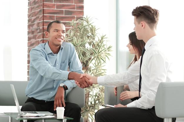 Handshake manager i klient w nowoczesnym biurze. koncepcja współpracy