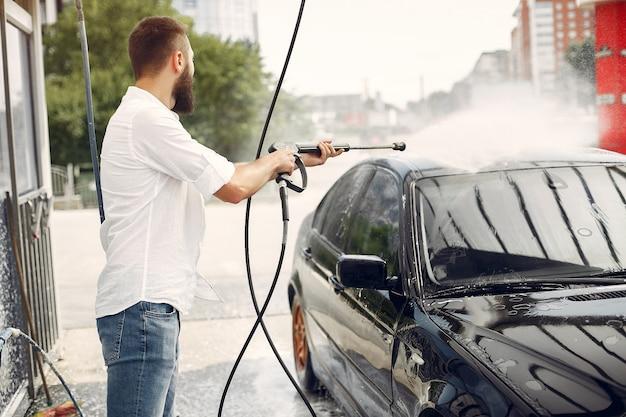Handsomen mężczyzna w białej koszuli mycie samochodu