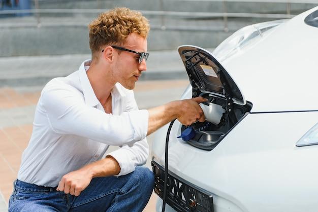 Hansome facet siedzi obok swojego nowego nowoczesnego samochodu elektrycznego i trzyma wtyczkę ładowarki, podczas gdy samochód ładuje się na stacji ładującej