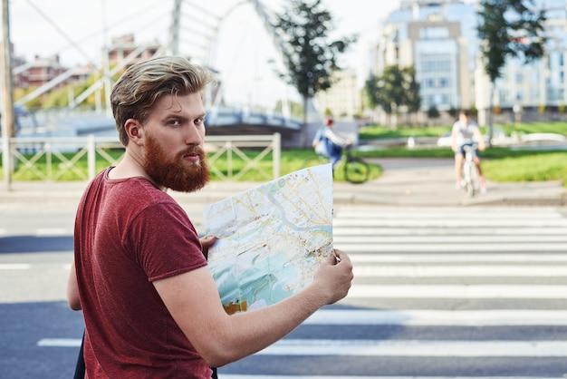 Hansome mężczyzna z dużą brodą w czerwonej koszulce spaceruje po mieście, aby dowiedzieć się więcej na jego temat