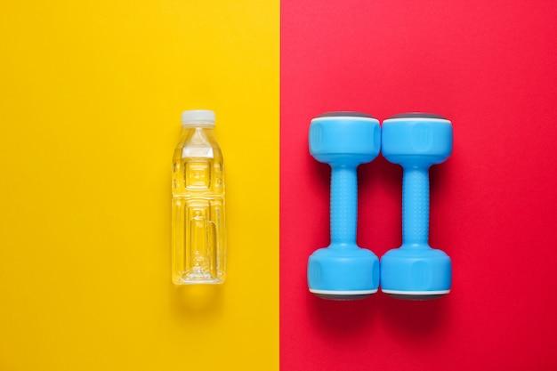 Hantle, butelka wody na kolorowej powierzchni.