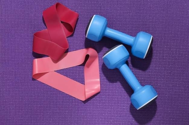 Hantle i gumki fitness na fioletowej macie sportowej. koncepcja treningu.