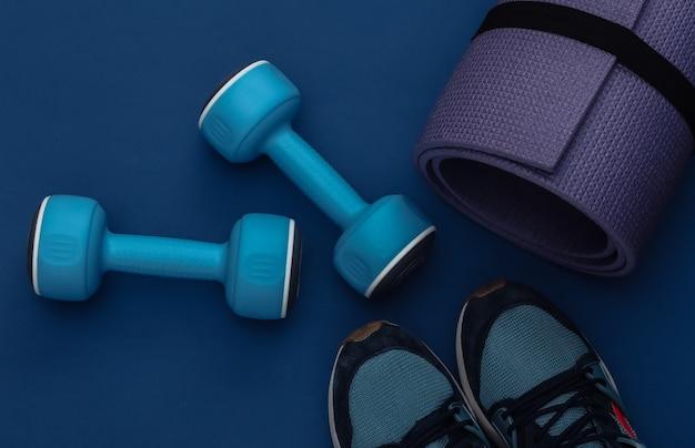 Hantle, mata fitness i trampki na klasycznym niebieskim tle. zdrowy styl życia, trening fitness. kolor 2020. widok z góry. płaskie ułożenie