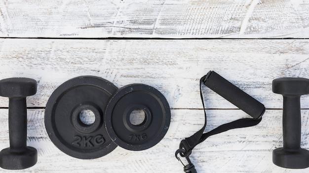 Hantle; płyty wagi i pasek fitness na białym drewnianym tle z teksturą
