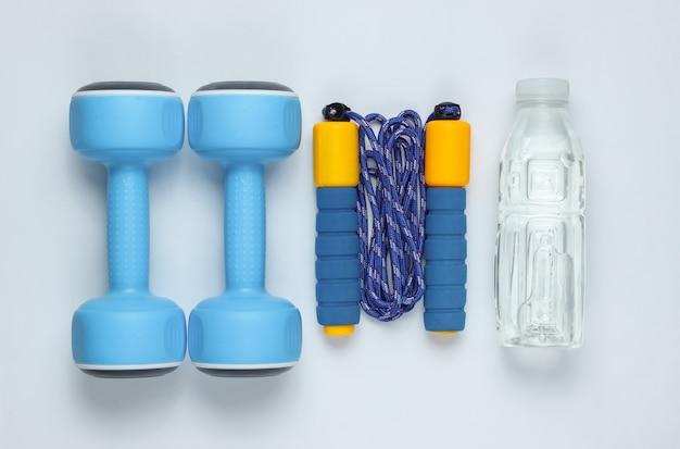 Hantle, skakanka, butelka wody. sprzęt sportowy na białym tle. widok z góry