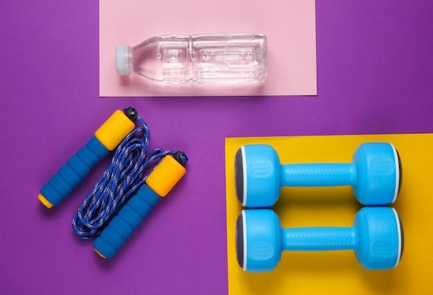 Hantle, skakanka, butelka wody. sprzęt sportowy na kolorowym tle.