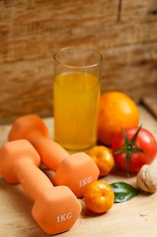 Hantle, sok pomarańczowy, owoce i orzechy na drewnianym stole, sport i koncepcja stylu życia zdrowia
