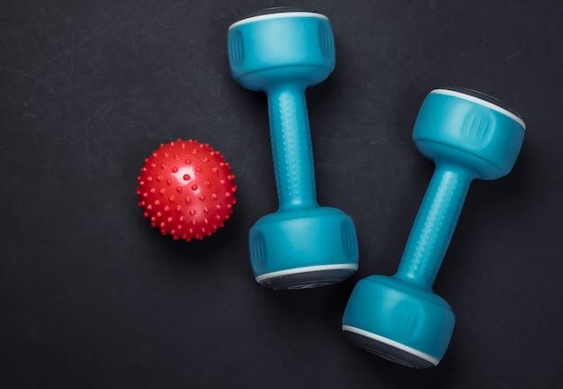 Hantle z piłką do masażu na czarno. fitness, koncepcja zdrowego stylu życia