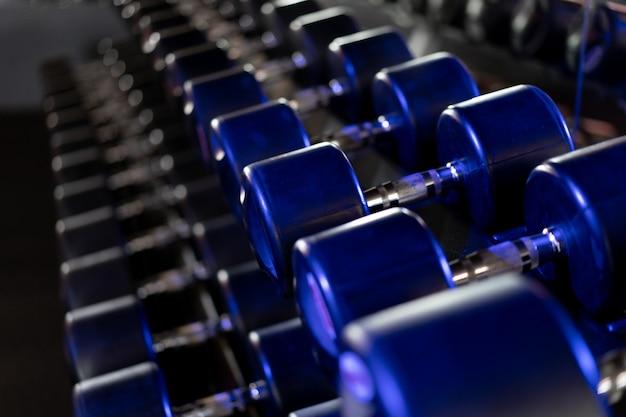 Hantle z rzędu na siłowni ciemny stonowanych koncepcja fitness zdrowego stylu życia