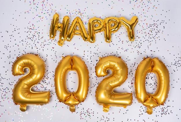 Happy 2020 napis sfrustrowanych złotych balonów na białym tle z kolorowymi konfetti