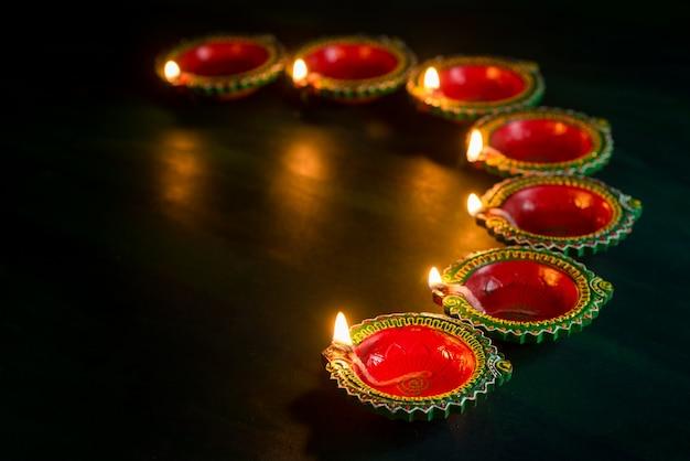 Happy diwali - lampy clay diya zapalone podczas obchodów diwali. projekt karty z pozdrowieniami indyjskiego hinduskiego festiwalu światła o nazwie diwali