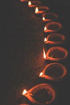 Happy diwali - wiele lamp z terakoty lub lamp naftowych ułożonych na glinianej powierzchni lub ziemi w jednej linii lub zakrzywionej lub zygzakowatej formie, selektywne skupienie