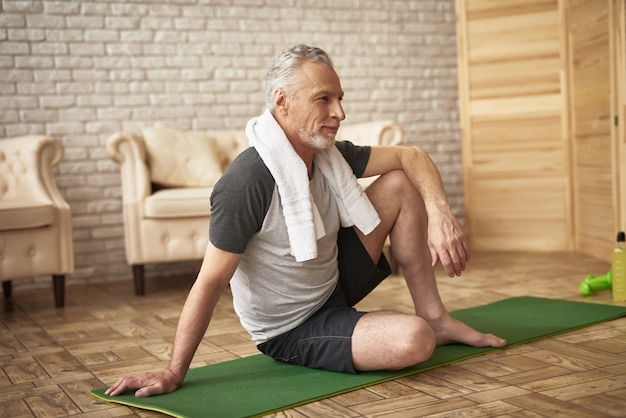 Happy elderly man on mat exercises for retired.