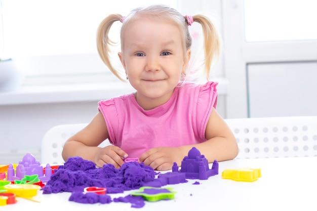 Happy girl gra w piasku kinetycznym w kwarantannie. blond piękna dziewczyna uśmiecha się i bawi się fioletowym piaskiem na białym stole.