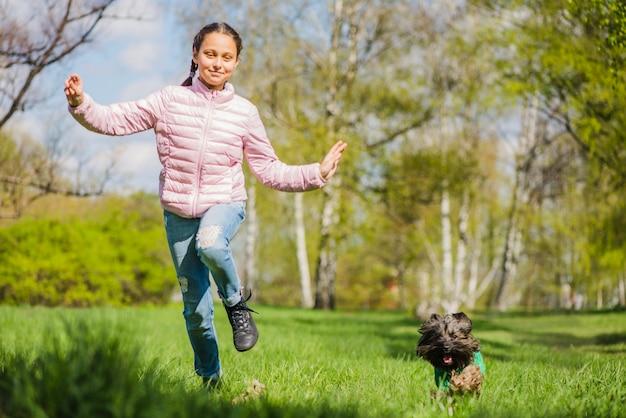 Happy girl gry z jej psa w parku