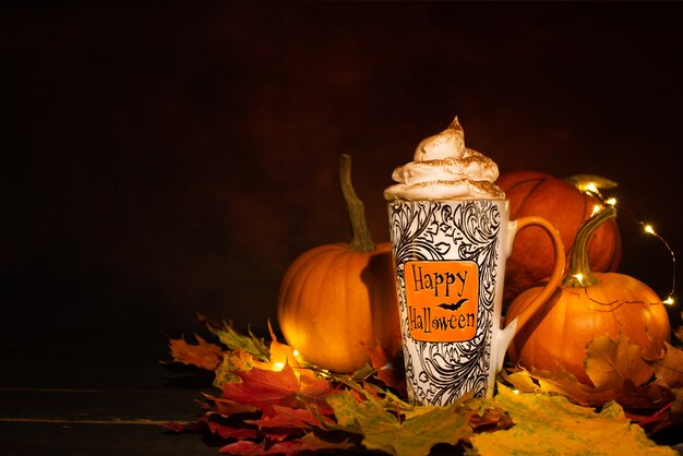 Happy halloween kubek z szeptaną śmietaną przed pomarańczowymi dyniami na ciemnym tle.