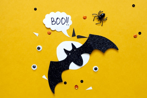 Happy halloween wakacje koncepcja. czarne nietoperze z papieru brokatowego i księżyc na jasnożółtym tle z czarnym pająkiem, oczami, konfetti. kartkę z życzeniami na halloween. pisownia słowa boo.