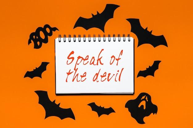 Happy halloween wakacje koncepcja. notatnik z tekstem mów o diable na biało-pomarańczowym tle z nietoperzami, dyniami i duchami
