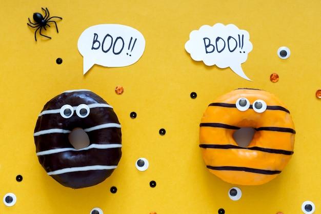 Happy halloween wakacje koncepcja. śmieszne jedzenie dla dzieci - przestraszone pączki jasnożółte tło z czarnym pająkiem i oczami. kartkę z życzeniami na halloween. pisownia słowa boo flat leżał, widok z góry, narzut.