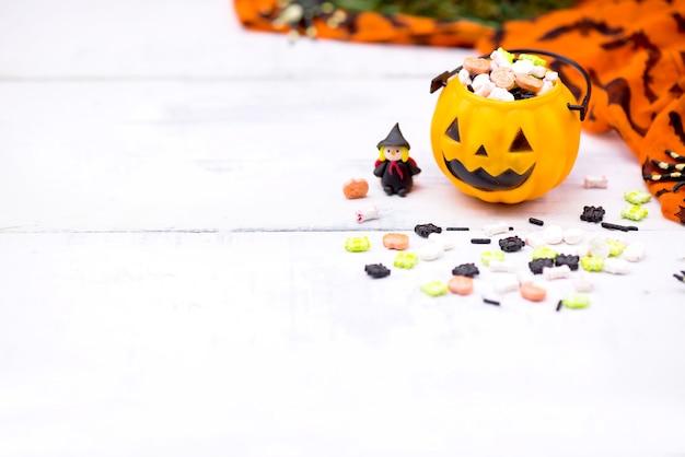 Happy halloween z cukierkami i dynią na imprezę. cukierek albo psikus w sezonie jesiennym.