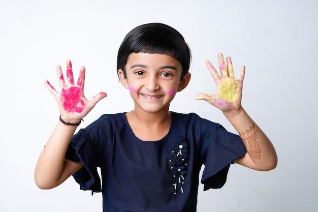 Happy holi greeting - cute little girl indian z kolorowymi rękami, odizolowane na białym tle