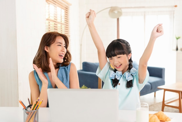 Happy homeschool azjatyckich mała młoda dziewczyna student uczenia się siedzi na stole w pracy z matką w domu.