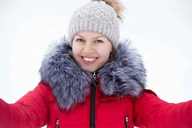Happy m? odych kobiet w czerwonej kurtce zimowej przy autoportret, na zewn? trz przeciwko? niegu