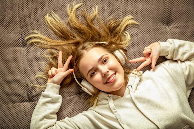 Happy millennial teen dziewczyna leżąc na wygodnej kanapie zabawy w ruchu, słuchając muzyki w słuchawkach. cute młoda kobieta korzystających z słuchania piosenek. widok z góry nastolatek dziewczyna uśmiech przepływające blond włosy.