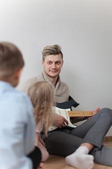 Happy młody ojciec z jego gitara