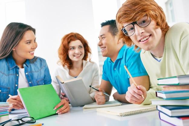 Happy nastolatek trzyma ołówek ze znajomymi tle