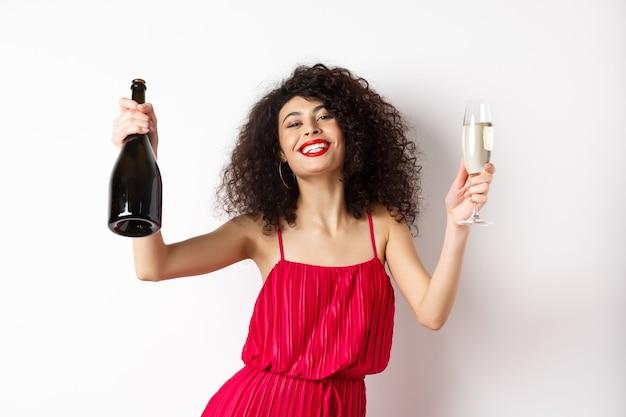 Happy party girl w czerwonej sukience, taniec z butelką szampana i szkła, picie i zabawę, obchodzi wakacje, stojąc na białym tle.