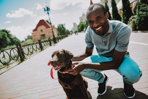 Happy positive black man walking brown doggy