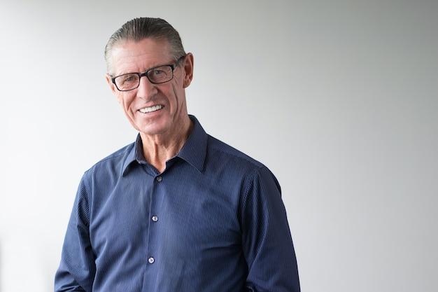 Happy starszy mężczyzna ubrany okulary uśmiecha się do kamery