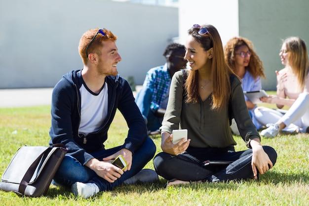 Happy studentów siedzących na zewnątrz w kampusie na uniwersytecie.