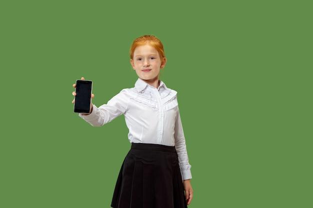 Happy teen girl stojącej, uśmiechając się z telefonu komórkowego na modnym zielonym tle studio.