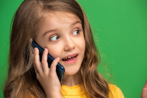 Happy teen girl stojącej, uśmiechając się z telefonu komórkowego na modnym zielonym tle studio
