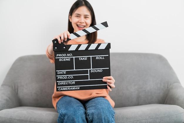 Happy uśmiechnięta azjatycka kobieta trzyma pokładzie filmu klakier i siedzi na kanapie.