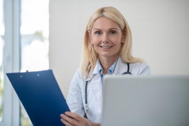 Happy uśmiechnięta kobieta lekarz siedzi z folderem w swoim biurze w ciągu dnia
